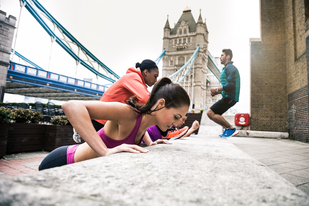 Athletic people exercising in London close to Tower Bridge.